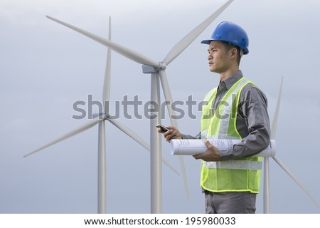 Portrait of a male Chinese industrial engineer at work checking winturbines.