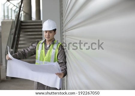 Portrait of a male Chinese industrial engineer at work looking at technical drawing plans.