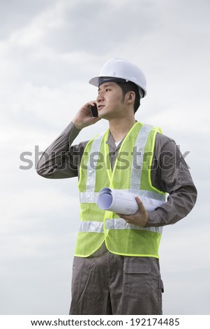 Portrait of a male Chinese industrial engineer at work using phone.