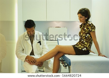 Portrait of a male doctor examining a young woman's feet
