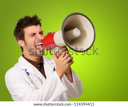 Portrait Of A Male Doctor Shouting On Megaphone On Green Background