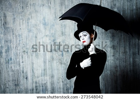 Shutterstock Portrait of a male mime artist standing under umbrella expressing sadness and loneliness. Grunge background.