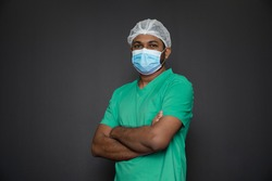 Portrait of a male nurse standing with arms folded isolated on a black background. Asian Nurse looking at camera. Male nurse with protective face mask against corona virus epidemic COVID-19