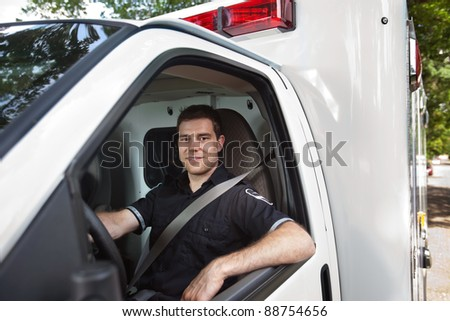 Portrait of a male paramedic sitting in driver seat of white ambulance