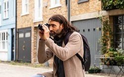 Portrait of a male photographer who is taking photos in a small alley in London, United Kingdom