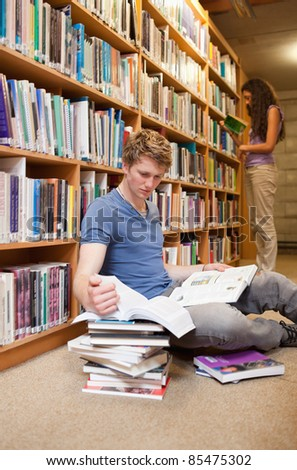 Portrait of a male student making research while his classmate is reading in a library