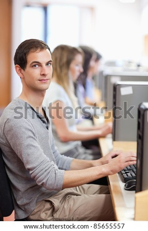 Portrait of a male student posing with a computer in an IT room