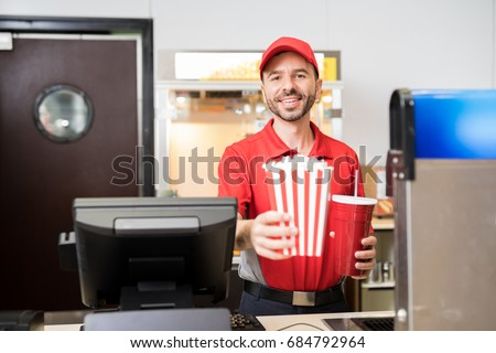Portrait of a male worker in uniform selling popcorn and soda at the concession stand in a movie theater