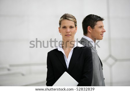 Portrait of a man and a woman holding a laptop computer
