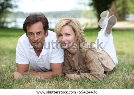 Portrait of a man and a woman laid in grass