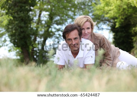 Portrait of a man and a woman laid in grass - stock photo