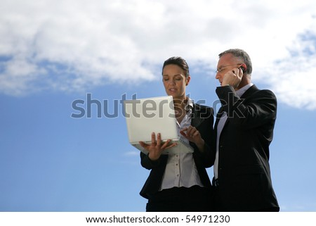 Portrait of a man and a woman with a laptop computer and a phone
