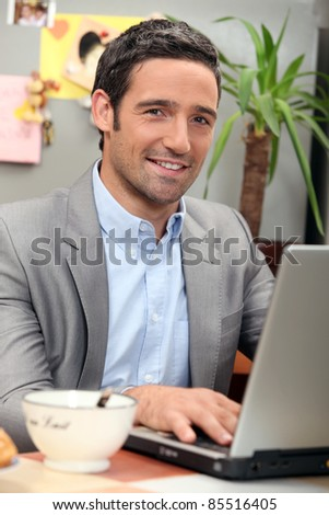 portrait of a man at breakfast with laptop
