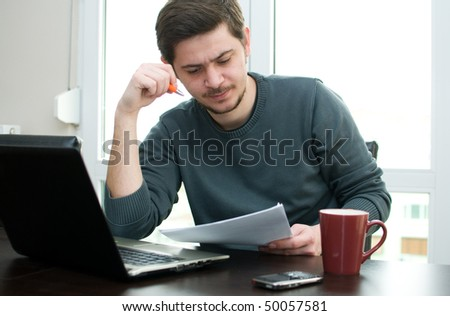 Portrait of a man at home working on a laptop