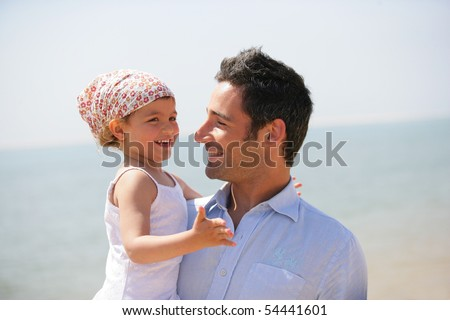 Portrait of a man carrying a little girl in his arms