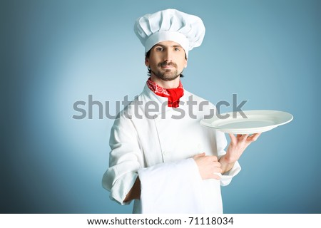 Portrait of a man cook holding a plate. Shot in a studio over grey background.
