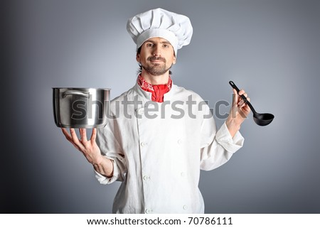 Portrait of a man cook holding a saucepan and ladle. Shot in a studio over grey background.