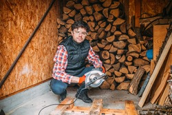 portrait of a man cutting wood with a circular saw, cutting wood for the fireplace, shed with wood