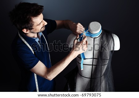Portrait of a man fashion designer working with dummy at studio.