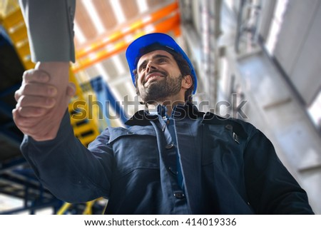 Portrait of a man giving an handshake in an industrial facility - Shutterstock ID 414019336