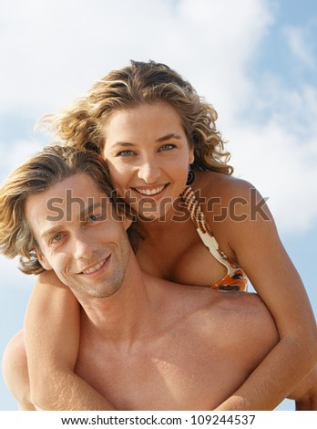 Portrait of a man having fun with his girlfriend while being playful on the beach.