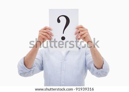 Portrait of a man hiding his face behind a question mark against a white background Foto d'archivio ©
