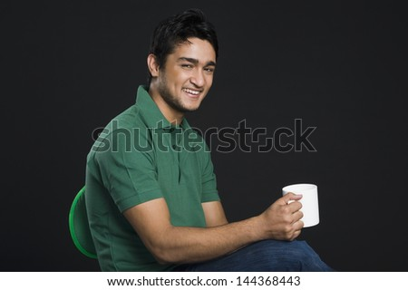Portrait of a man holding a cup of coffee - stock photo