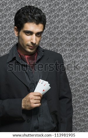 Portrait of a man holding three aces