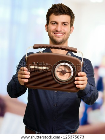Portrait Of A Man Holding Vintage Radio, Indoors
