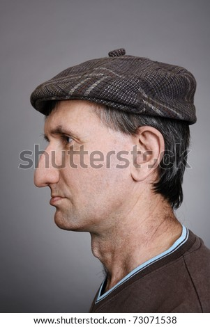 Portrait of a man in a cap in profile on a gray background