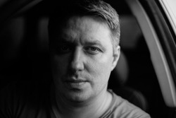 Portrait of a man in a car close-up in black and white tones. Monochrome photo. Low key.