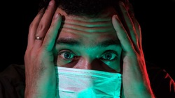 Portrait of a man in a medical mask. Isolation of the house in quarantine. The emotions of fear and impending doom. Global viral pandemic. The epidemic of coronavirus. Covid-19. 2019-nCoV.