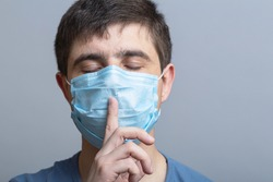 portrait of a man in a protective medical mask on face showing sign of silence gesture putting finger in mouth and lips, concept medical secrecy, moment of mourning and silence