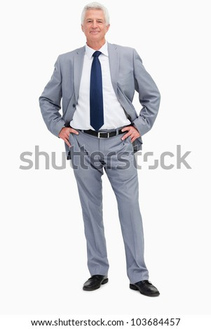 Portrait of a man in a suit with hands on hips against white background