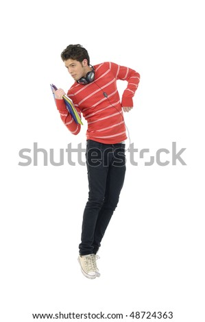 Portrait of a man in casual clothes jumping with headphones around his neck