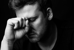Portrait of a man in depression on a black background