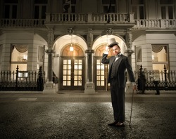 Portrait of a man in elegant suit standing in front of a palace