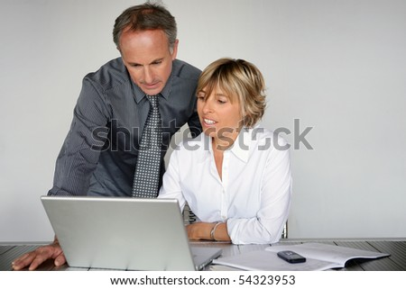 Portrait of a man in suit and a woman in front of a laptop computer