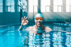 Portrait of a man in the pool. He is wearing huge funny glasses. Water sports concept. Mixed media