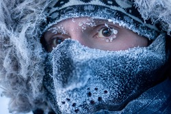 Portrait of a man in winter clothes and a mask. A traveler in the Arctic. Ice and snow on eyelashes, face and mask. Cold polar climate. Extreme travel and expeditions to the far North to the Arctic.