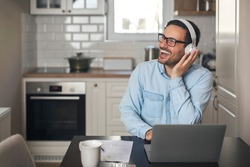 Portrait of a man listening music on headset and smiling while sitting in front of laptop.