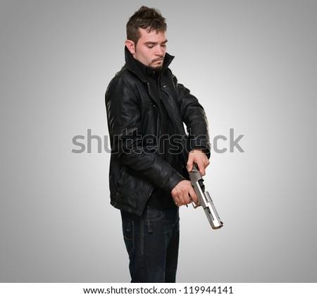 Portrait Of A Man Loading Gun against a grey background