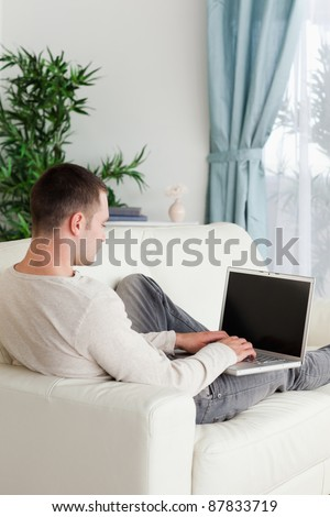 Portrait of a man lying on his couch using notebook in his living room