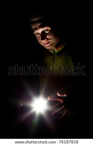 Portrait of a man on a black background with a bright light in his hands, in the style of magic