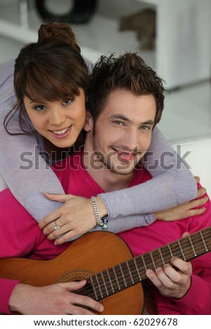 Portrait of a man playing guitar to his friend