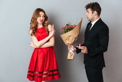Portrait of a man proposing to a girl with flowers and an engagement ring and getting denied over gray wall background