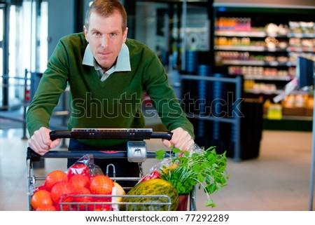 Portrait of a man pushing a grocery cart in a supermarket