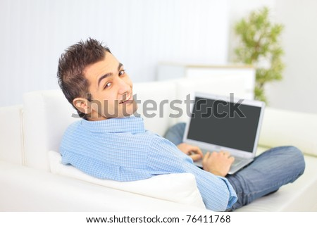 Portrait of a man relaxing on couch while using a laptop