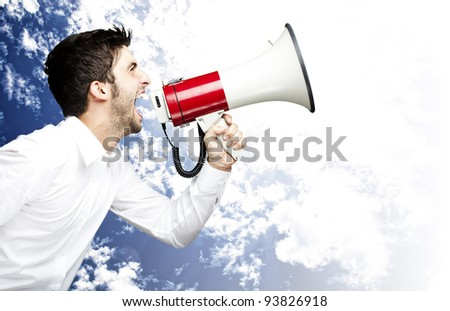 portrait of a man shouting with a megaphone against a sky background