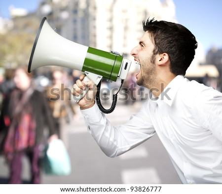 portrait of a man shouting with a megaphone against a street background